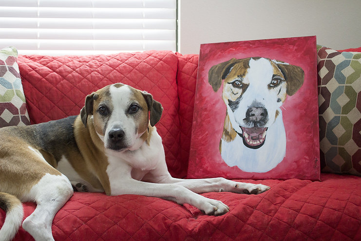 beagle mix sitting in front of a portrait of herself