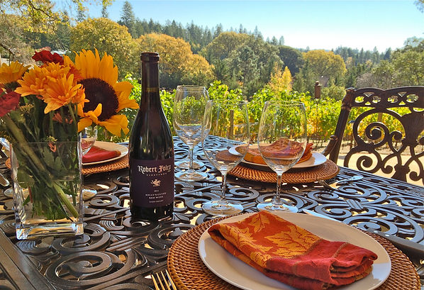 A bottle of Robert Foley Syrah set on a table with glasses overlooking the vineyard