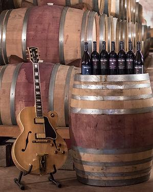 Guitar displayed next to Robert Foley wine bottles