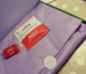 A close up photo of the inside of a cross stitch kit box:  purple tissue paper is folded over, covering the contents.  The paper is secured with a sticker, bearing the Fandom Cross Stitchery logo.  Resting on top of the tissue paper are an individually wrapped Lotus Biscoff biscuit, and a 'Lyons No. 4' coffee bag.  The background is taupe with white polka dots.