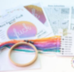 A 'mini pastel fuck cross stitch kit'.  In the left foreground is a small square of white Aida fabric, and a small bamboo embroidery hoop.  On the right is a rectangle of white card withsymbols and codes on the right hand side, and holes punched down the left hand side.  Through each of the holes is a different coloured thread.  In the backgrund are the instructions for the 'mini pastel fuck' which feature a photo of the finished piece (pastel colours with a white, cursive 'fuck' in the centre).  Also in the background are basic, black and white instructions on how to cross stitch.