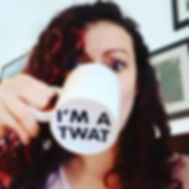 """Picture of Fandom Cross Stitchery owner, Helen, drinking from a mug.  The mug covers most of her face, and her eyes look slightly worried. On the bottom of the mug, in bold black text, it says """"I'M A TWAT""""."""