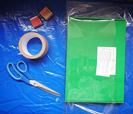On the right half of the photo is a green cross stitch kit box being wrapped in clear, compostable cellophane wrap.  On the box is a small slip of paper detailing the composition and disposal information of various parts of the kit and packging.  On the left hand side of the picture are: a stamp and ink pad, a roll of brown paper tape, and a pair of blue scissors.  The background is bright blue.