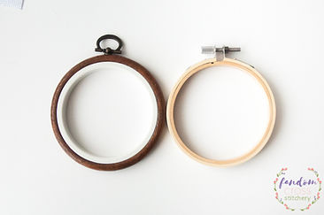 Two small embroidery hoops on a plain white background.  The left is a dark brown plastic, resembling wood, with a metal loop on the top.  The inner part is white.  The right hoop is a pale wooden bamboo with a metal screw on the top.  The Fandom Cross Stitchey logo is in the bottom right corner.