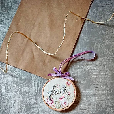 Image shows a small embroidey hoop with floral fabric and the word 'fuck' embroidered in silver brush script font.  It has a purple hanging ribbon tied in a bow at the top of the hoop.  It is resting on a brown paper bag with twine curling across the picture.