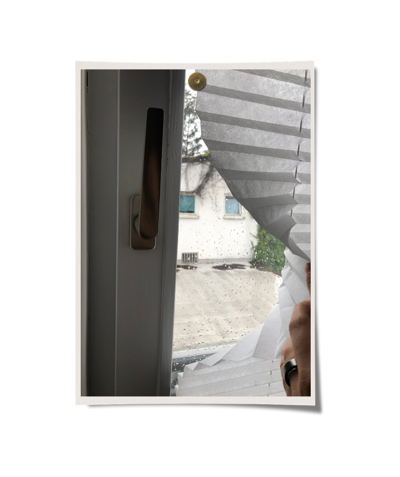 Fenster bei dem von einer Hand der Vorhang zurückgehalten wird. Man sieht, dass es regnet.