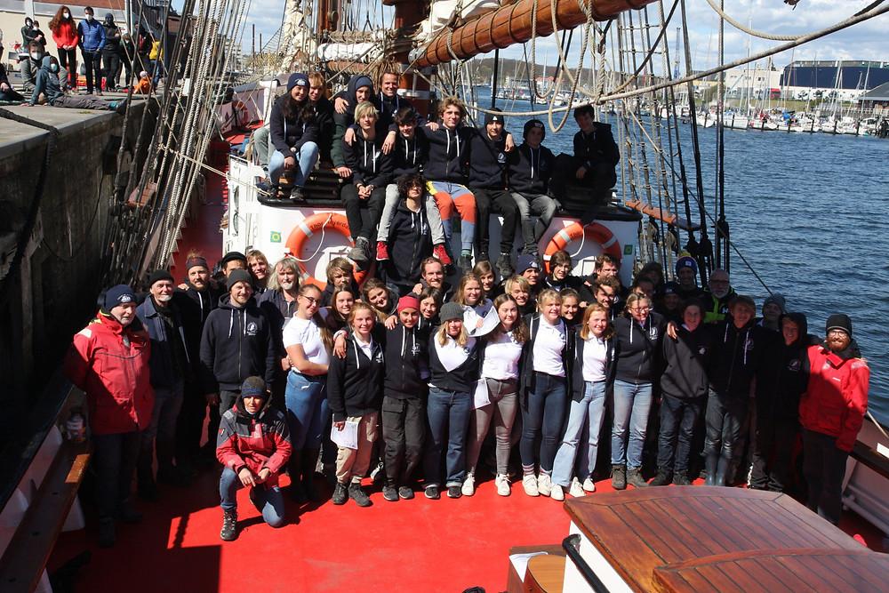 Gruppenbild auf Deck eines Segelschiffes.