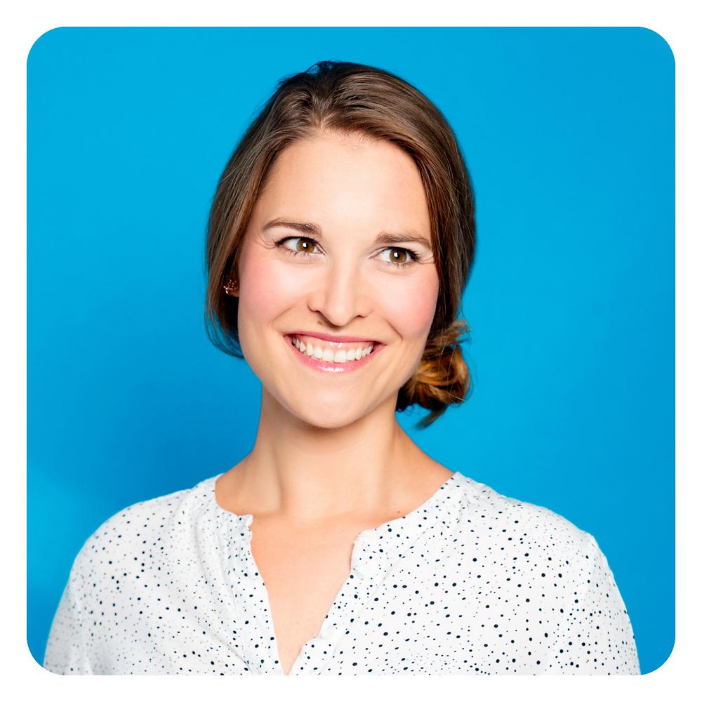 Zu sehen ist ein Portrait von mir, Franziska Blickle, lächelnd vor blauem Hintergrund.
