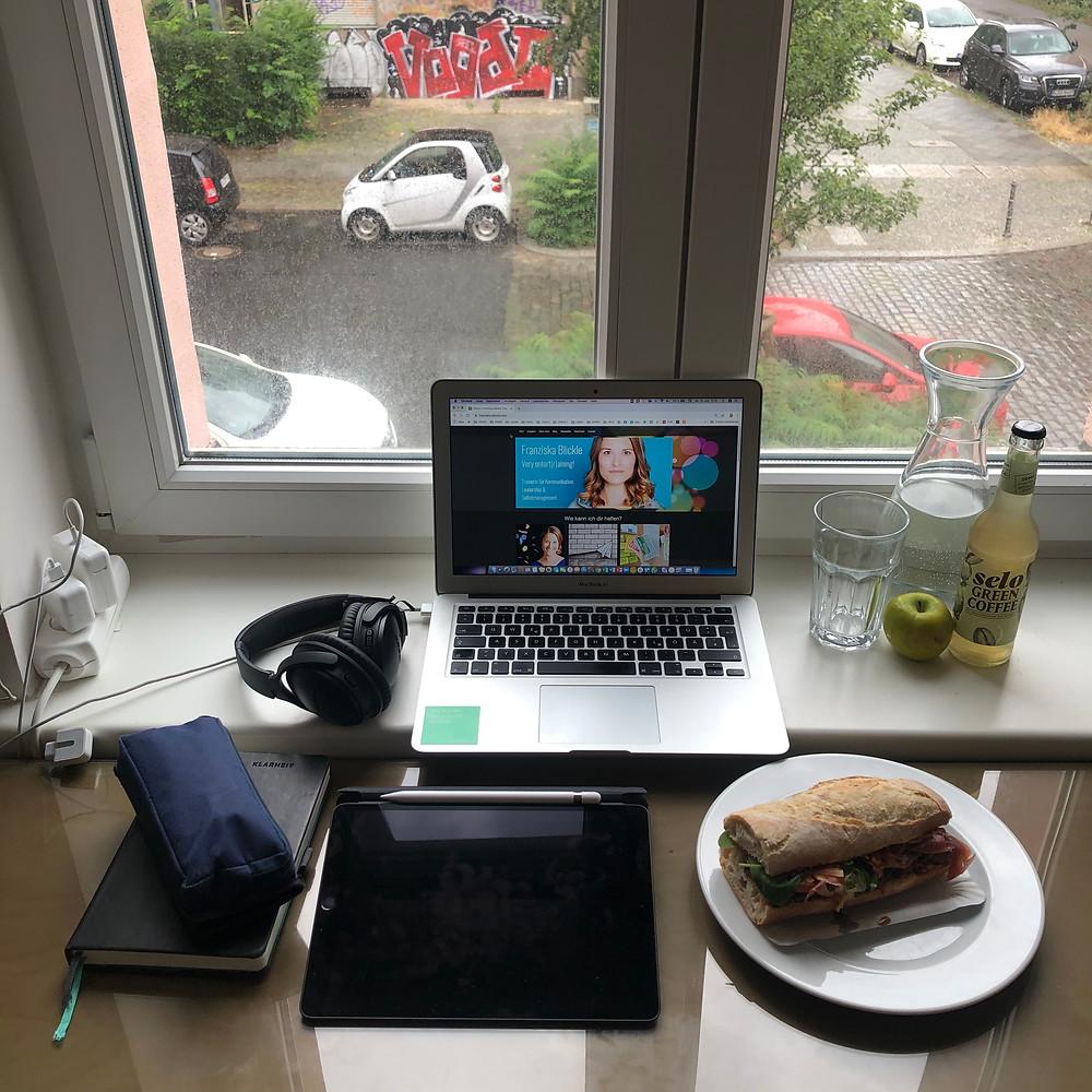 Schreibtisch vor einem Fenster, darauf liegen ein Laptop, Kopfhörer, ein Tablet, ein Teller mit einem Sandwich, ein Apfel eine Flasche Limo, eine Karaffe Wasser, ein Buch und ein Stiftemäppchen