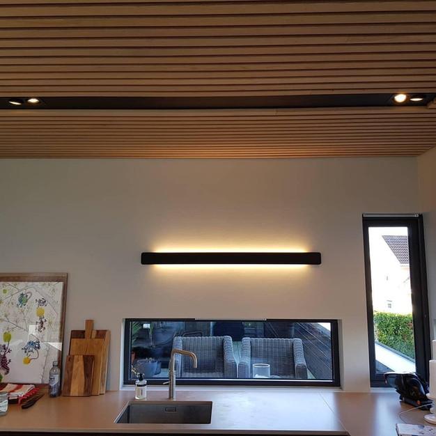 Nisje i tak med innfelt lys og designerlampe på vegg (Kjøkken)
