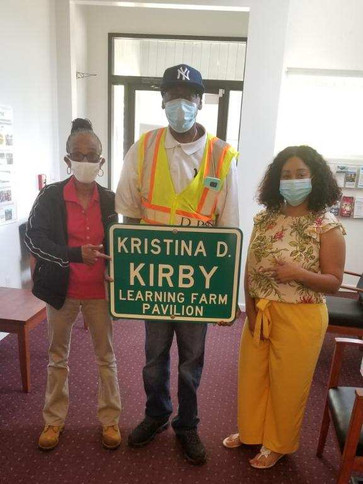 Staff holding learning farm sign.jpg
