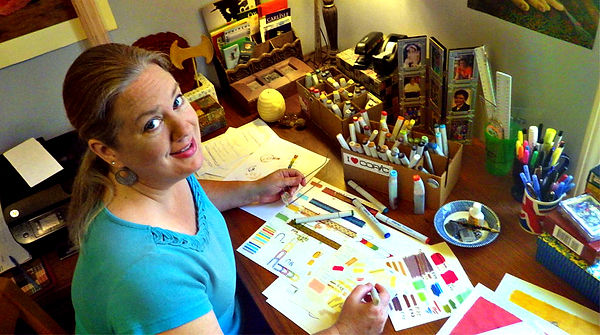 Photo of Laura Perry at her art desk surrounded by paints, markers, and other art supplies