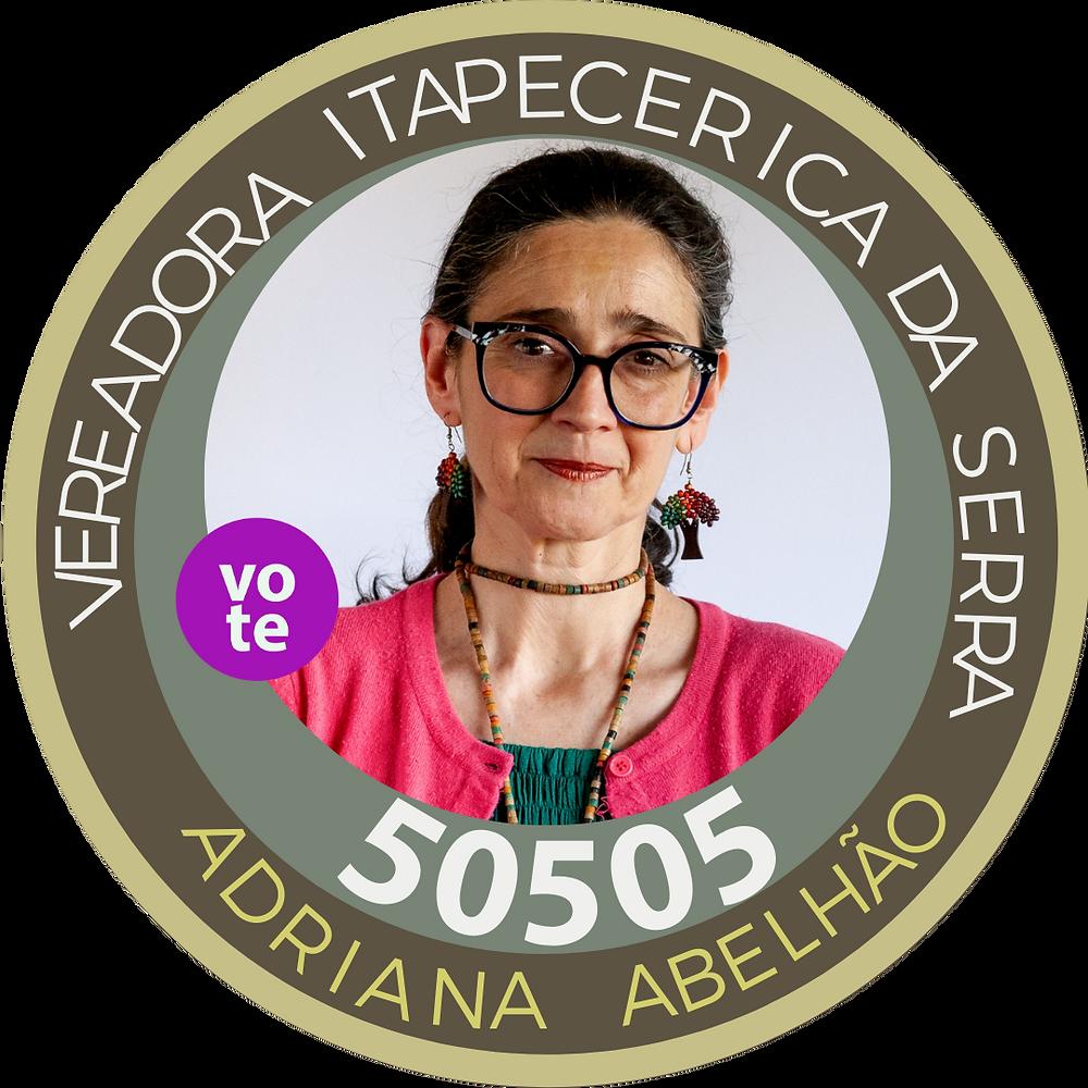 Foto da candidata Adriana Abehão. Ela usa óculos, colar e brincos em formato de árvore. Usa blusa rosa sobre uma blusa verde.