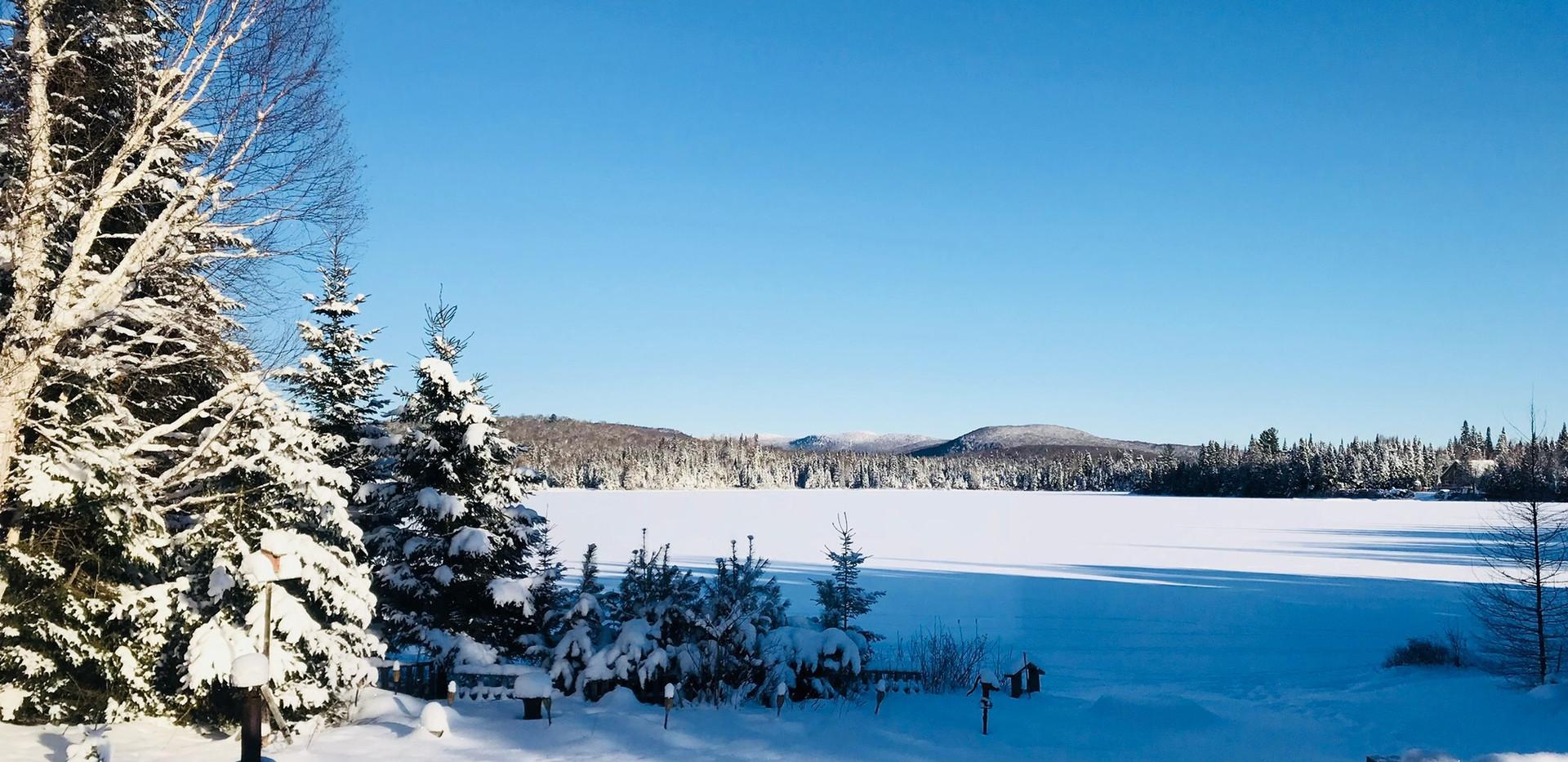 Chalet à louer au Québec | face au lac | 4 saisons Le Cocooning L'Ascension | Vue de l'intérieur en hiver