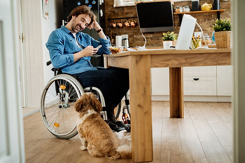 man in a wheelchair using the participant dashboard and smiling at his dog