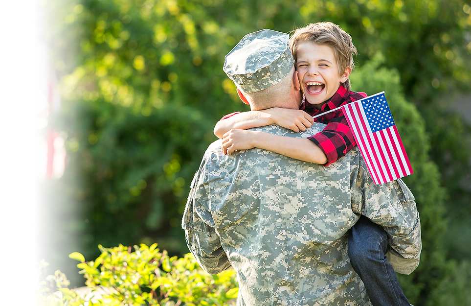 Happy child hugging man in soldier's uniform and holding an American flag