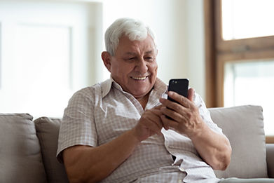 Elderly man using mobile phone to complete e-timesheets