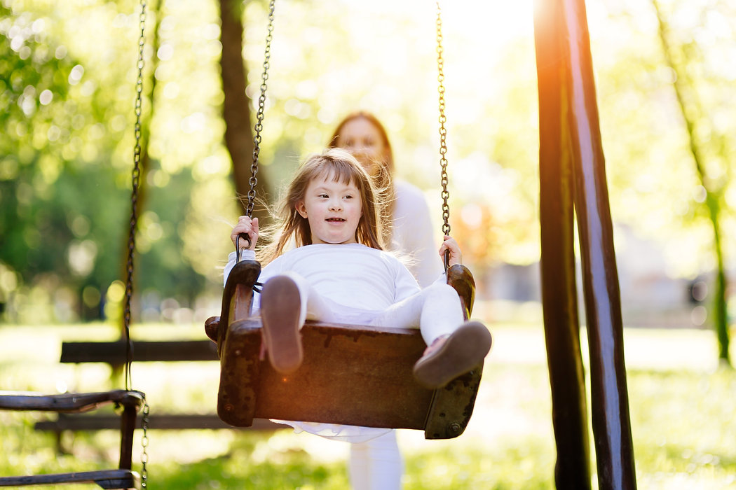 Girl on swing pushed by her mother