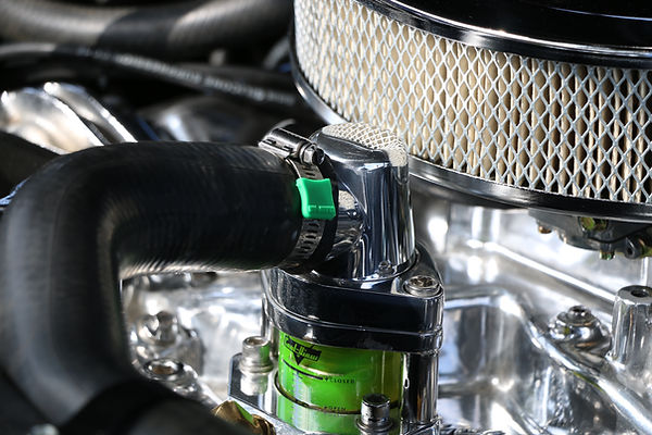 Restored Vintage Classic Oldsmobile station wagon with clear thermostat housing on engine an a automotive hose clamp with a green Clamp aid end cover