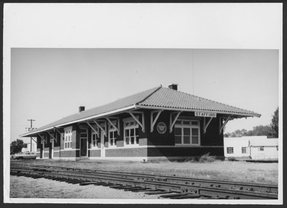 Missouri Pacific Railroad depot, Stafford, Kansas This photographs shows the Missouri Pacific Railroad Company's combination depot at Stafford, Kansas. The one-story brick structure features a pantile roof with massive brackets that brace the roof's overhangs. Date: 1971