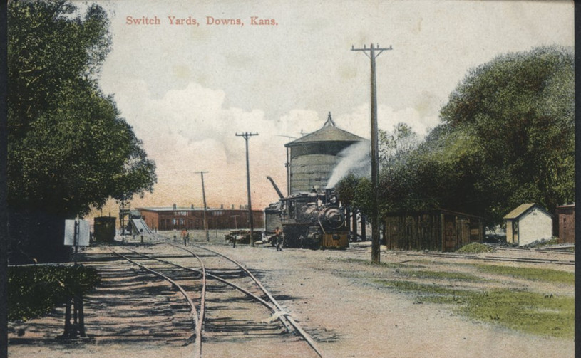 Missouri Pacific switch yards in Downs, Kansas This is a postcard showing a steam locomotive in the Missouri Pacific switch yards in Downs, Kansas.