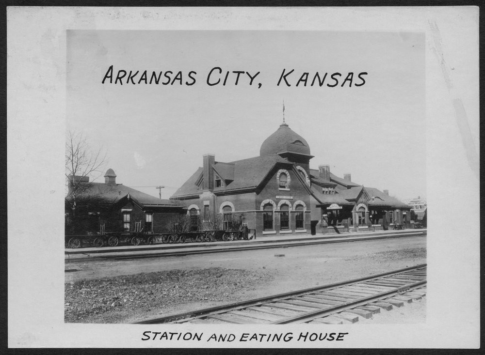 Atchison, Topeka and Santa Fe Railway Company depot, Arkansas City, Kansas  This photograph shows the Atchison, Topeka and Santa Fe Railway Company depot and eating house in Arkansas City, Kansas.  Creator: Atchison, Topeka, and Santa Fe Railway Company Date: Between 1890 and 1931