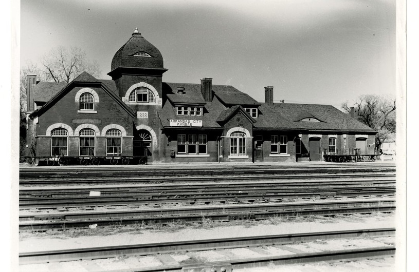 Atchison, Topeka and Santa Fe Railway Company depot, Arkansas City, Kansas  This photograph shows the Atchison, Topeka and Santa Fe Railway Company depot in Arkansas City, Kansas. The two-story red brick building was completed in 1888 and consisted of two waiting rooms, a dining room and a lunch counter. The depot was razed in 1950. A modern style depot was dedicated at the same location on April 27, 1951.  Creator: Atchison, Topeka, and Santa Fe Railway Company Date: Between 1940 and 1950