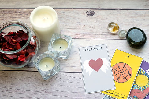 The Lovers ,Wheel of Fortune and The Sun cards on a white wooden table near candles and ge