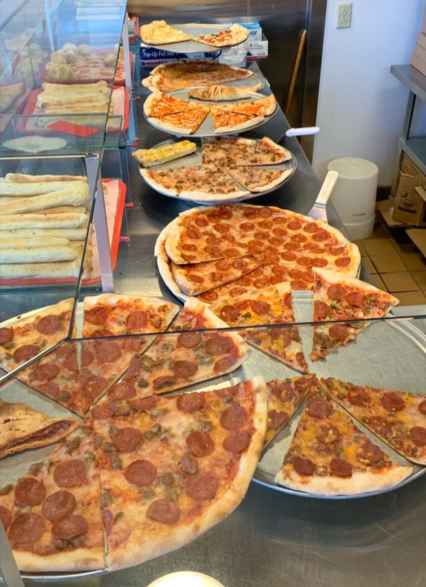 ready made pizzas on counter in pizza shop