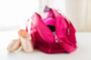 sport, fitness, ballet and objects concept - close up of pointe shoes and sports bag