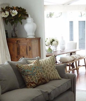 Interior Design. Living room with Andrew Martin sofa, bespoke cushions, wooden chest, glass vase with Magnolia leaves and flowers, white ceremic vase. Dining room with rustic wooden table, wooden bench seat, linen cahirs, white ceremic vases, glass vase with white Hydrangeas, wooden floors.