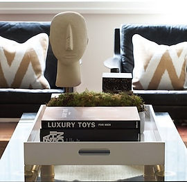 Beautifully styled room, black leather chairs, cream cushions with gold geometric stripe, brass and glass coffee table with head sculpture, white wooden tray, black books, black boxes and plant.
