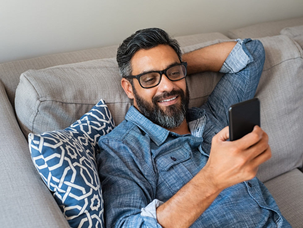 Happy smiling latin man using smartphone