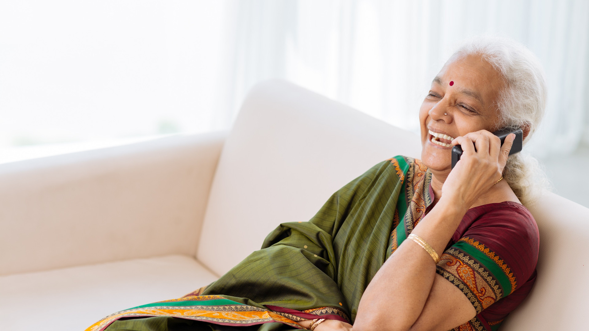 Laughing Indian woman with a telephone s