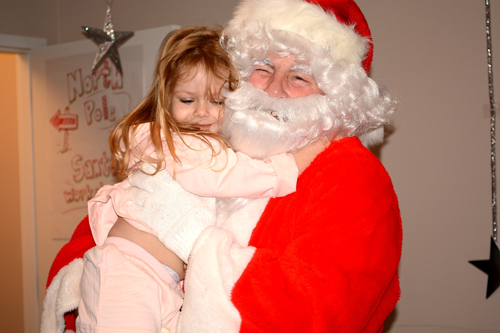 Aiyana, one of the many underserved children who attended, shows Santa her appreciation