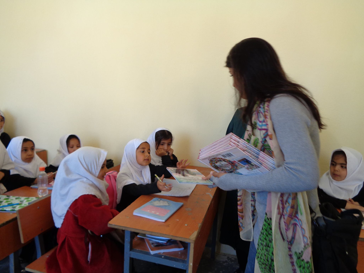 Sara Kazimi while distributing educational books to school students