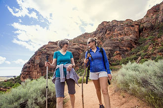 Two happy women hiking together in a red