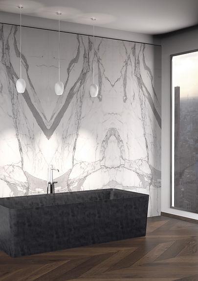 Ambiente bagno con rivestimento a macchia aperta della parete in marmo statuario e vasca Entity Cono bath in pietra lavica a massello.