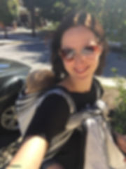 White woman with dark brown hair and sunglasses smiles taking a selfie wearing a black tshirt and a black and white wrap. Her baby is on her back and his head is tucked against her back so you only see his blonde hair.