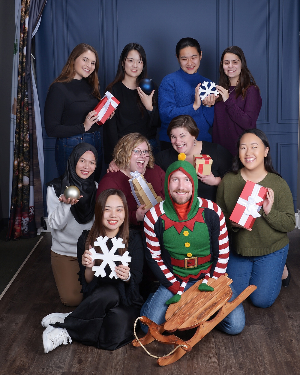 Ten diverse members of the TTP team are huddled in a group for the winter holiday photo. Everyone is holding a present, ornament, snowflake, or other winter-themed item, and one guy is dressed in a red and green elf suit.