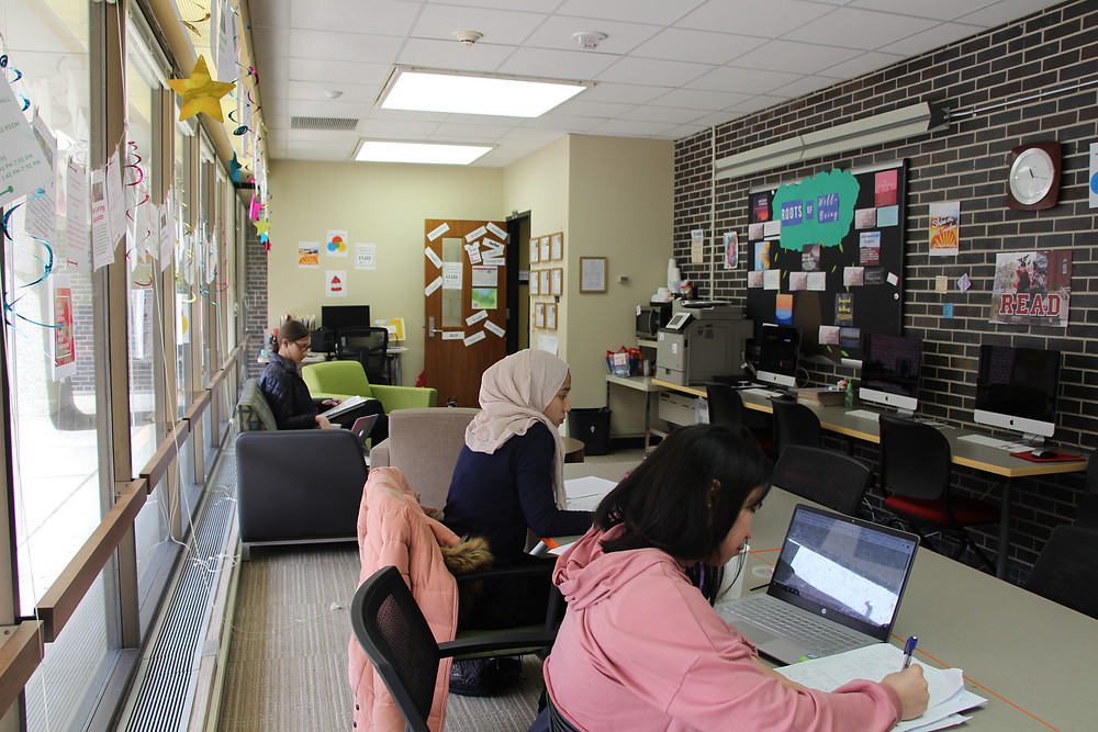 A wall lined with windows allows light to spill into the long narrow space. The opposite wall is exposed brick and is covered in colorful flyers. There are several Mac computer stations, and three students sit in the space, using their laptops and working on class assignments..