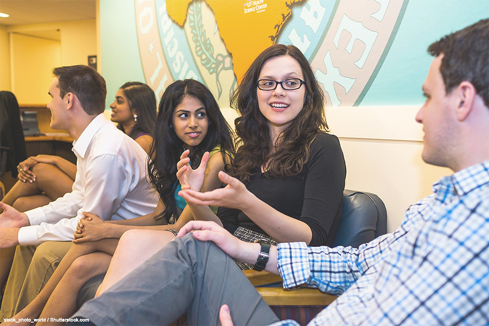 A multi-ethnic, multi-gendered group of college students sits together in the Student Center. Two distinct groups are chatting with each other. The camera is focused on one adult female who is gesturing with her hands as she speaks to one male and one other female.