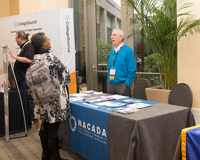 Dr. Grites stands behind the NACADA information table and speaks to a conference participant at the NISTS 2020 annual conference in Atlanta, Georgia.
