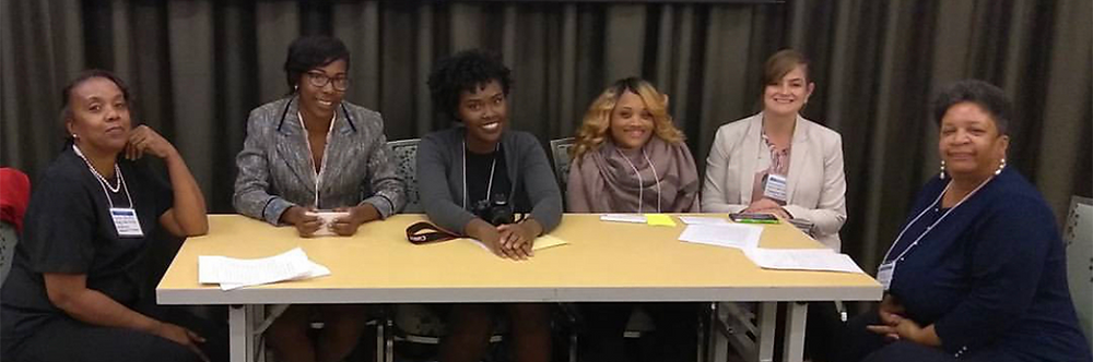 Keirra sitting at a presenter's table with three other students and two faculty