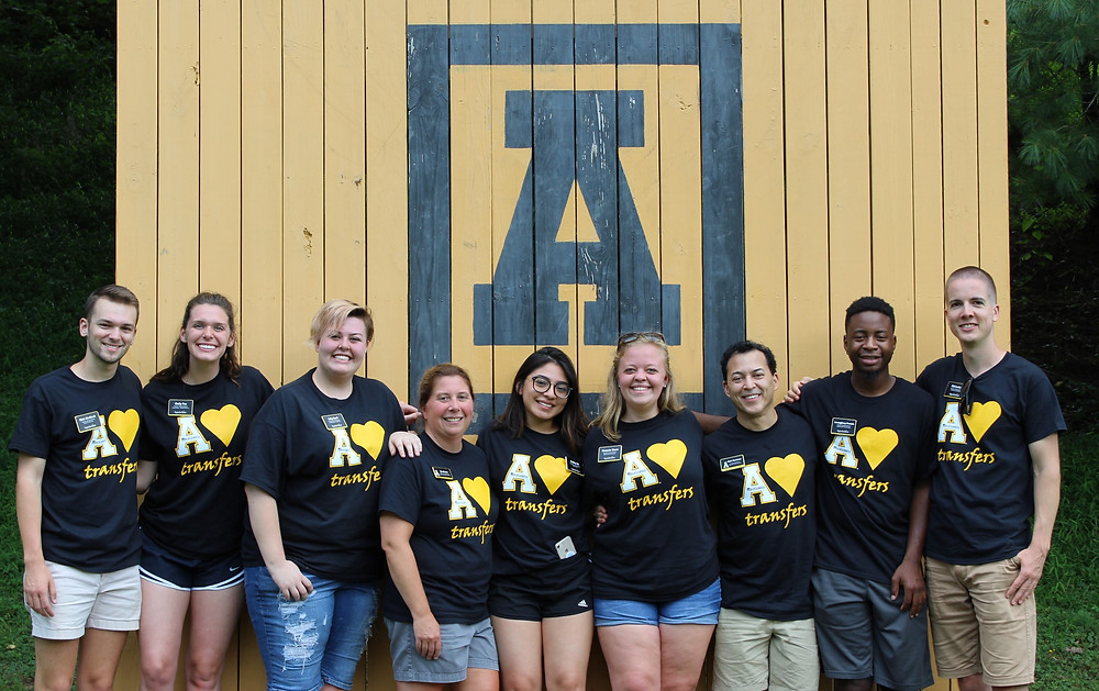 "Staff and Transfer Student Mentors in Appalachian State University's Office of Transfer Services wearing black and gold ""Appalachian loves transfers"" T-shirts pose for a photo at the university's Camp Broadstone facility in Valle Crucis."