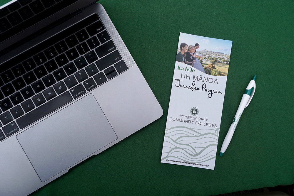 A brochure for the UH Manoa Transfer Program sits on a green table top next to a pen and an open laptop.