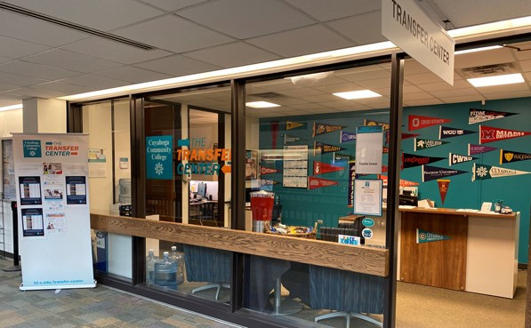 The transfer center features an all glass front wall so that passers by can see directly into the center. Behind the reception desk, a variety of college pennants are hung on the wall, illustrating the many regional and national transfer options students have.