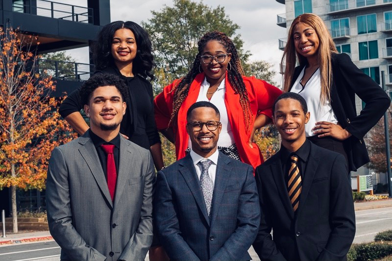 Michael poses with five other students of the Collegiate 100. All are formally dressed in suits.