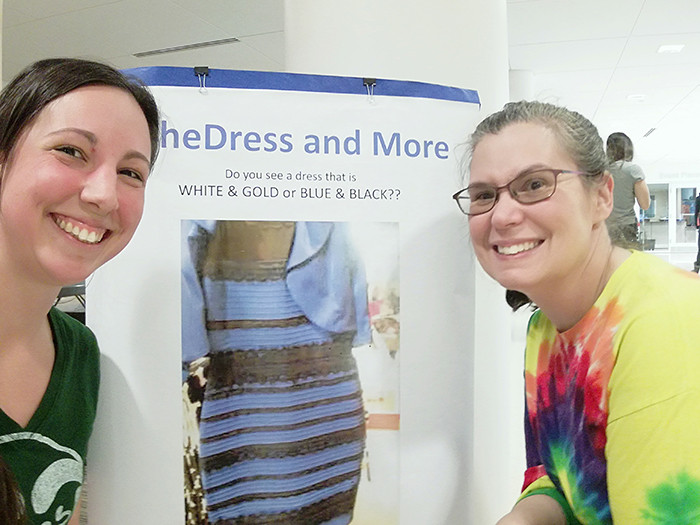 Emily and a friend pose in front of a poster advertising the infamous White & Gold or Blue & Black dress debate.