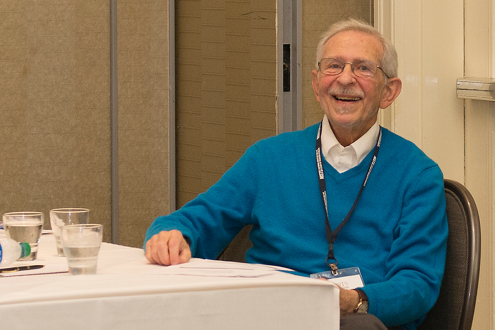 Dr. Tom Grites smiles at the camera from behind the presenter's table at the NISTS 2020 annual conference in Atlanta, Georgia.